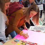 People writing signs for the National Day of Action 2019