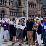 People stand in a row holding banners and signs for International Overdose Awareness Day outside of a large brick building in Toronto
