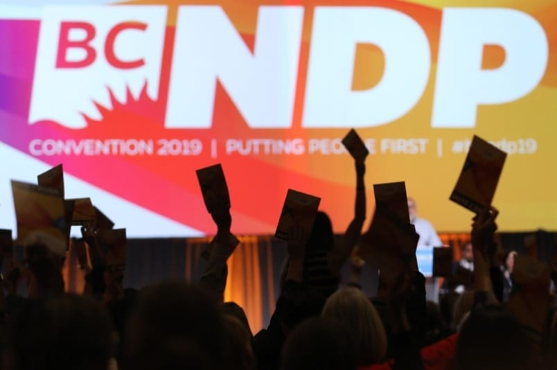 hands holding up voting cards in front of a large overhead screen displaying NDP logo