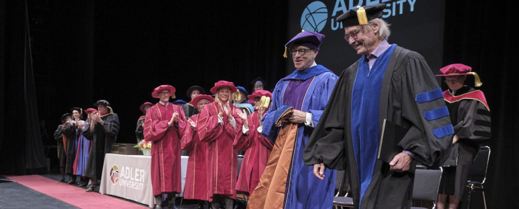 Two men walk off stage in robes and Adler University's commencement ceremony for their class of 2019