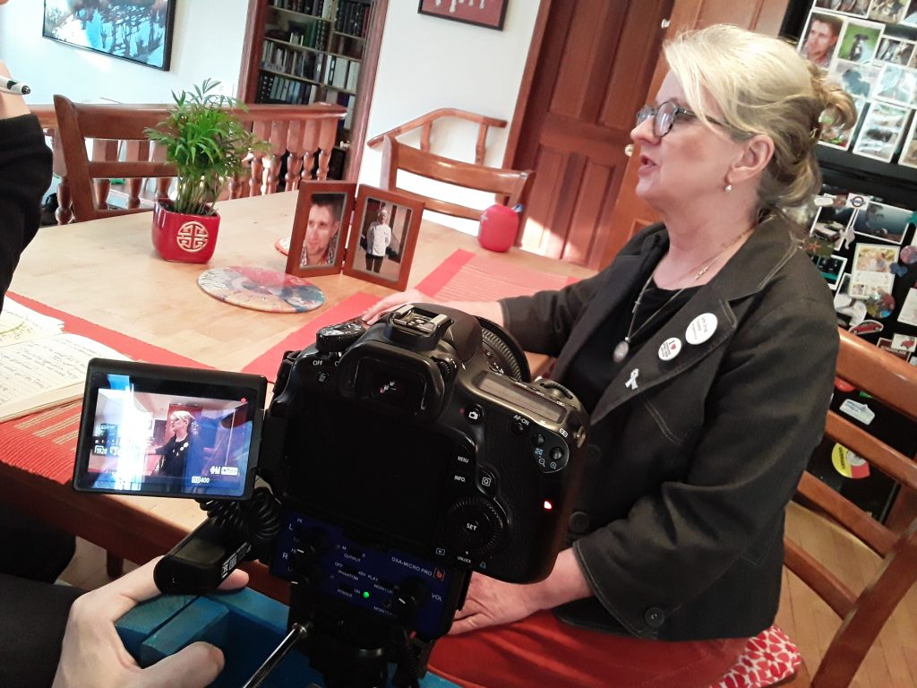 Woman sitting at kitchen table being interviewed by film crew