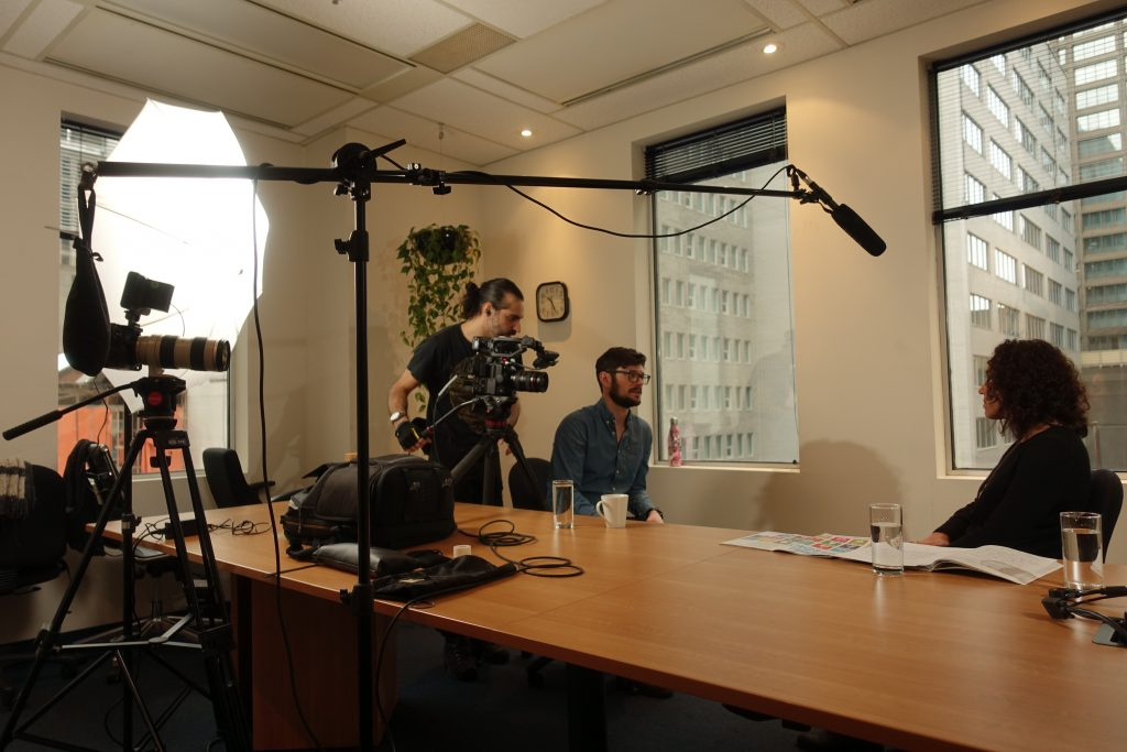 Woman sitting at a table being interviewed by a film crew