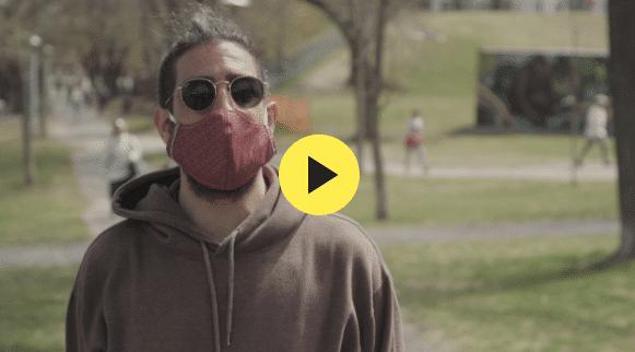 Man in a brown hoodie wearing a mask
