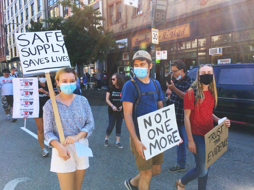 Two people walking down Hastings Street carrying protest signs during VANDU memorial march
