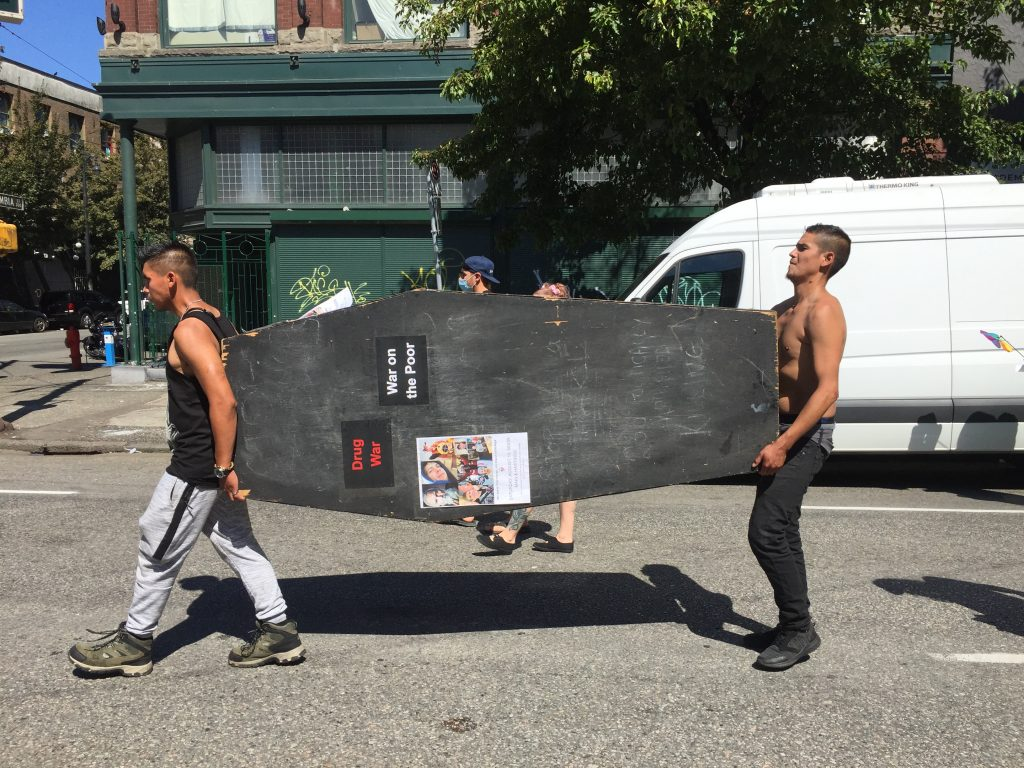 Two men carrying a large black wooden coffin down a street