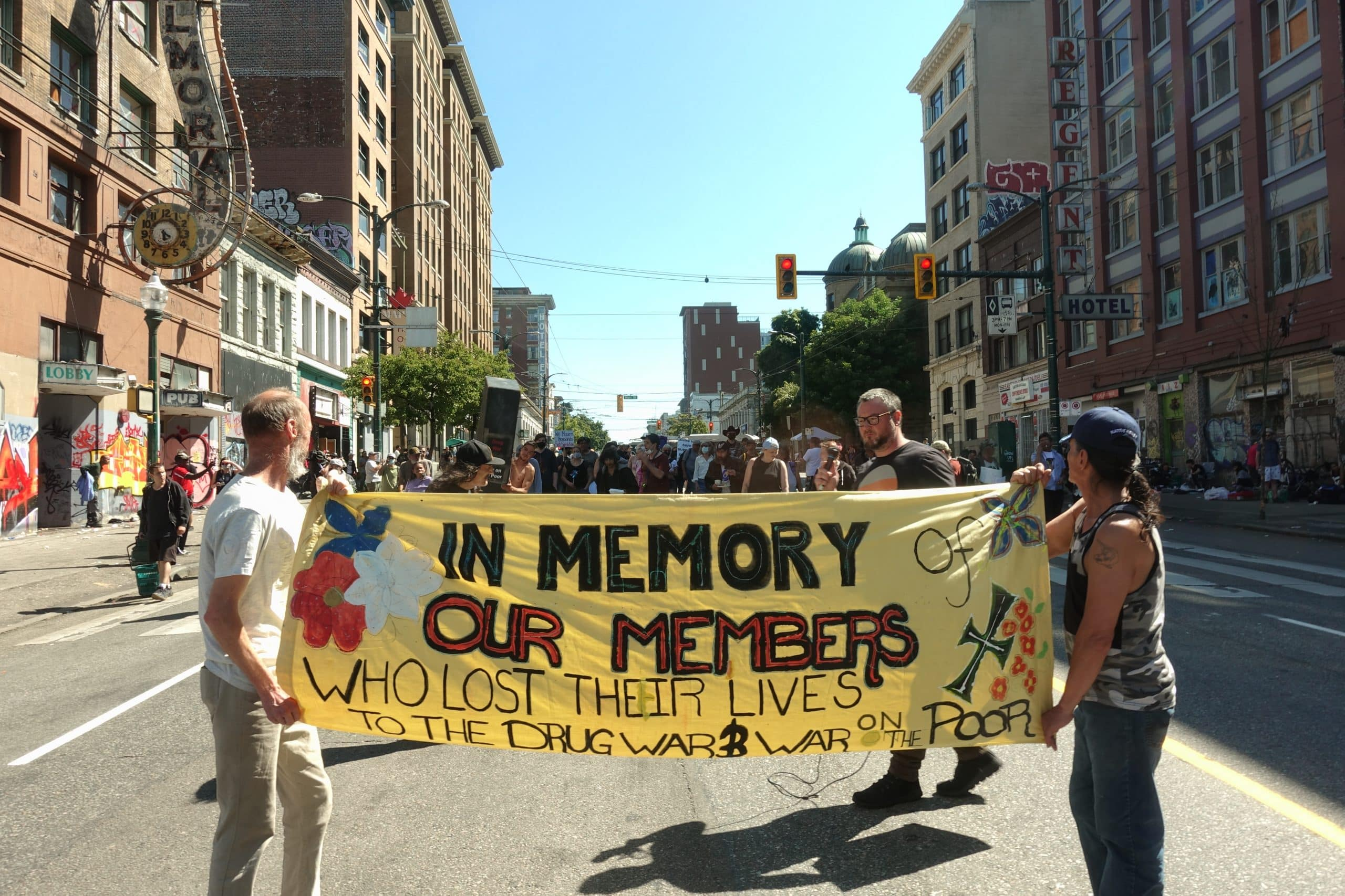 """Two people carry a large banner down the street that reads """"In Memory Our Members"""""""