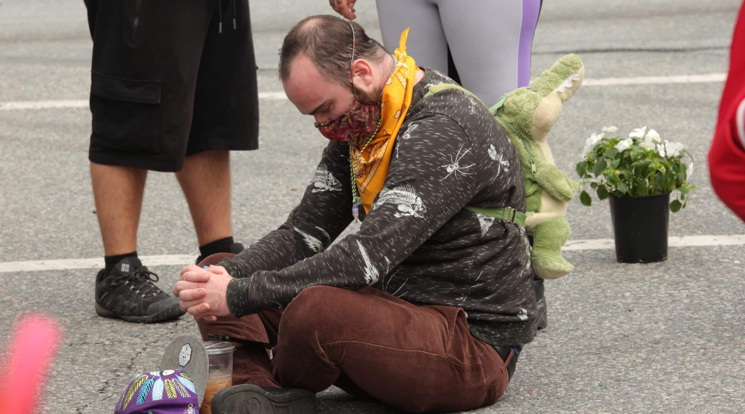 A mourner sits on the ground at a rally in Vancouver