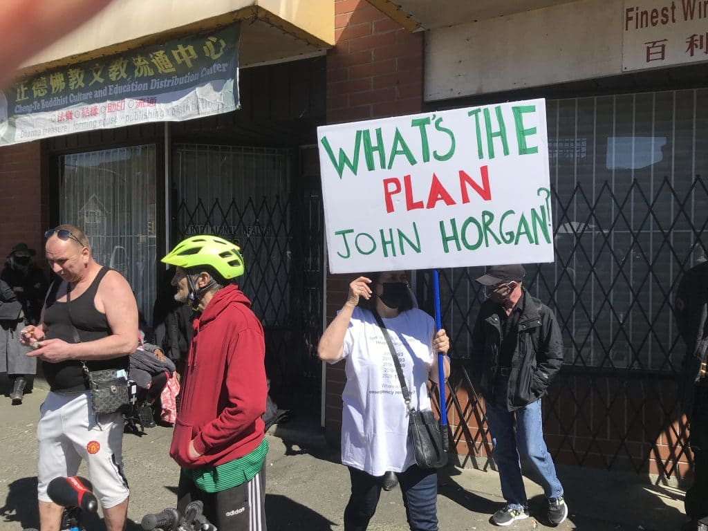 Person holding a protest sign at a rally