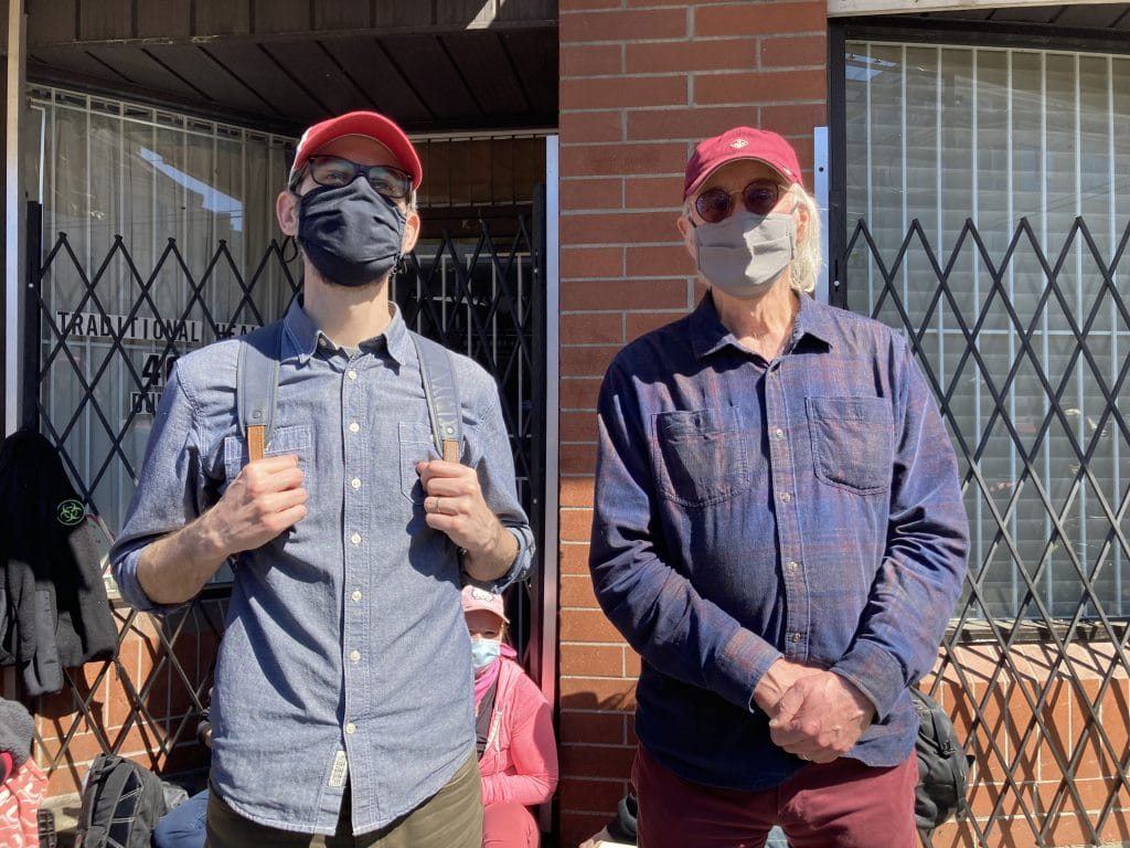 Two men wearing COVID-19 face masks