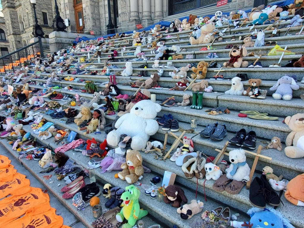 Teddy bears and childrens shoes lining the steps of the BC Legislature