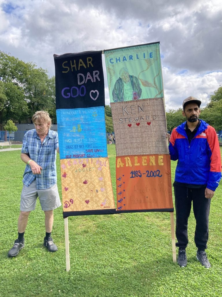 Two people holding a sign made of quilts