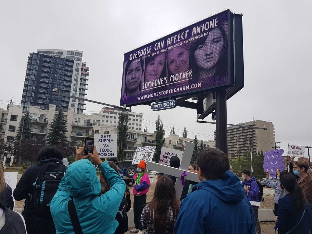 Large purple billboard showing faces of those who have died from overdose