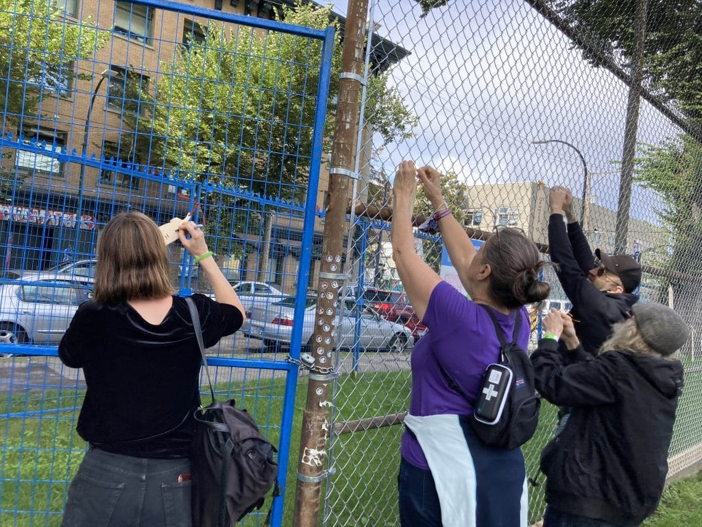 Three people tyding wooden feathers to a fence
