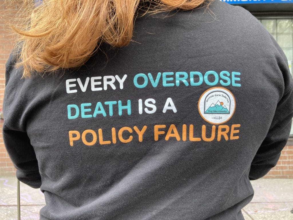 """The back of a sweater with slogan reading """"every overdose death is a policy failure"""""""